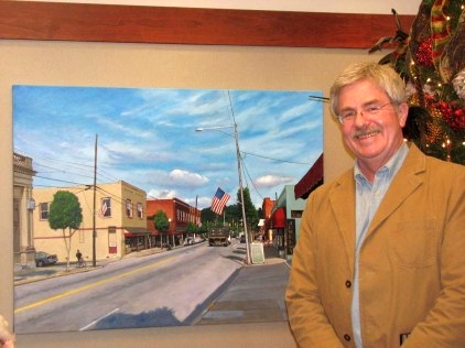 Doug Strickland stands by his painting 'Clayton Main Street' on display at the Capital Bank office in Clayton, NC